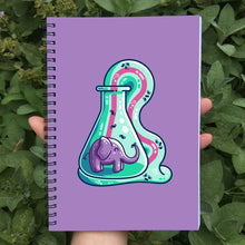 Load image into Gallery viewer, Closed notebook showing the purple front cover and elephant toothpaste design