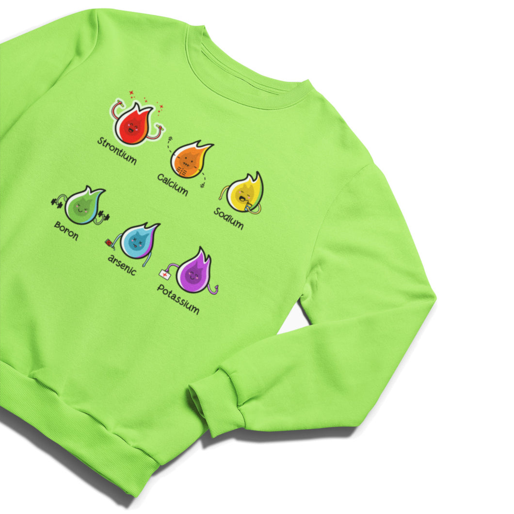 A lime green unisex crewneck sweatshirt laid flat with a design on its chest of two rows of three kawaii cute flames representing strontium in red holding flow sticks, calcium in orange with skeletal bones, sodium in yellow drinking through a straw, boron in green lifting weights, arsenic in blue dead with a bottle of poison, and potassium in purple carrying a first aid box