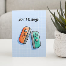 Load image into Gallery viewer, A blue greeting card standing on a white table with a design of an orange and a turquoise game controller and the words your message written above