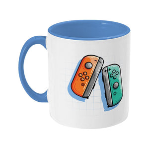 An orange and a turquoise game controller design on a two toned navy and white ceramic mug, showing LHS