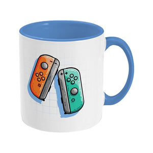 An orange and a turquoise game controller design on a two toned navy and white ceramic mug, showing RHS