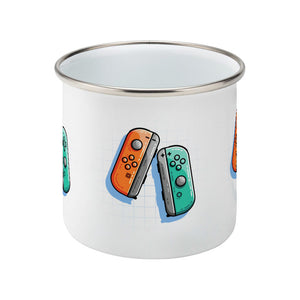 An orange and a turquoise game controller design on a silver rimmed enamel mug, side view