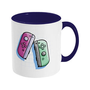 A pink and a green game controller design on a two toned navy and white ceramic mug, showing RHS