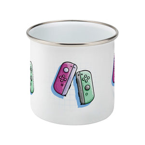 A pink and a green game controller design on a silver rimmed enamel mug, side view