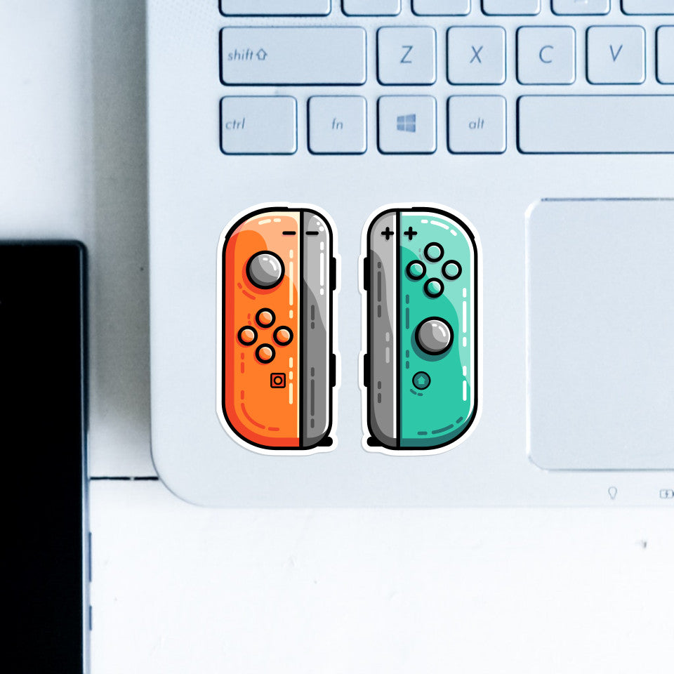 A pair of orange and green gaming controllers stuck side by side on the botto left hand corner of a computer keyboard