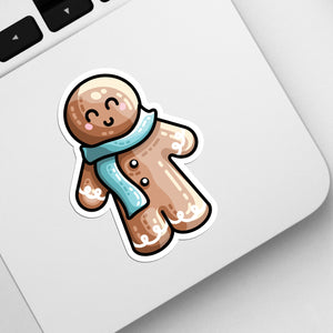 The corner of a laptop keyboard with a die cut vinyl sticker of a cute gingerbread person wearing a blue scarf stuck onto it