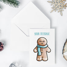 Load image into Gallery viewer, An open white envelope beneath a white greeting card with a design of a kawaii cute gingerbread person wearing a blue scarf