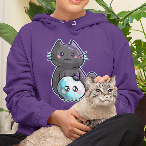 Torso of a woman sitting with a cat in her lap wearing a purple hoodie with the neck cords tucked in and a design on the chest of a kawaii cute black cat with a paw resting on top of a blue tinted kawaii cute skull