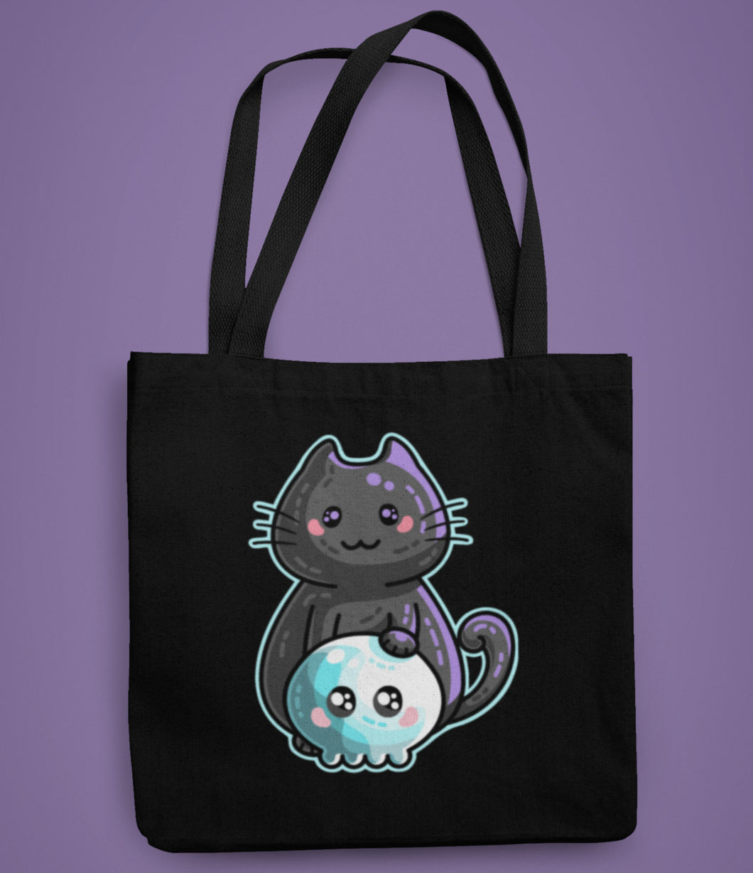 A dark blue coloured fabric tote bag lying flat against a purple background with a design in the center of a kawaii cute black cat with its paw resting on a kawaii cute skull.