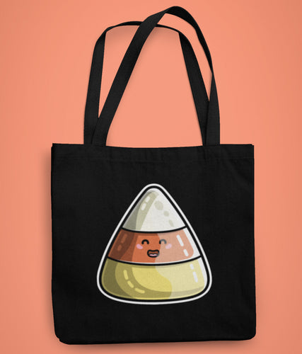 A black coloured fabric tote bag lying flat against an orange background with a design in the center of a cute smiley faced striped candy corn sweet in white orange and yellow printed in the center of the bag.