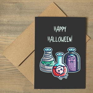 A dark grey greeting card with the words happy halloween, lying flat on a brown envelope, with a design of three glass bottles in halloween costume as a mummy wrapped in bandages with green liquid, a vampire in a black cape with purple liquid, and a skull with bones in red liquid