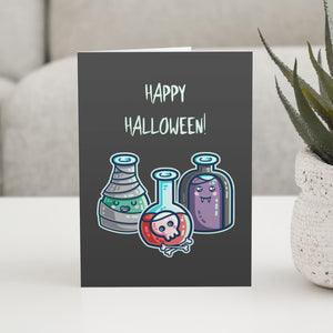 A dark grey greeting card with the words happy halloween, standing on a white table, with a design of three glass bottles in halloween costume as a mummy wrapped in bandages with green liquid, a vampire in a black cape with purple liquid, and a skull with bones in red liquid