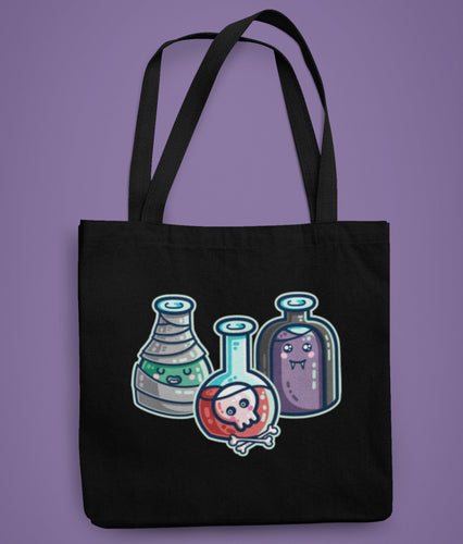 A black coloured fabric tote bag lying flat against a purple background with a design in the center of three glass bottles of green, red and purple liquid in halloween fancy dress with mummy bandages, skull and bones, and vampire cape.