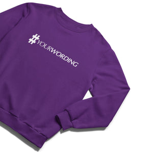 A purple crewneck sweatshirt with a white print of a large hash symbol followed by italic capital letters saying YOUR WORDING