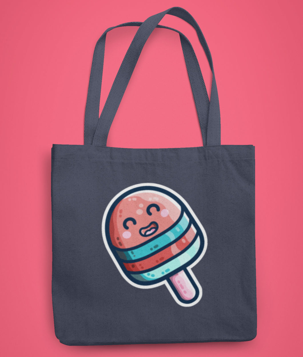 A dark blue coloured fabric tote bag lying flat against a pink background with a design in the center of a kawaii cute striped blue and red ice lolly on a stick with a big happy smile and bordered with a white line.