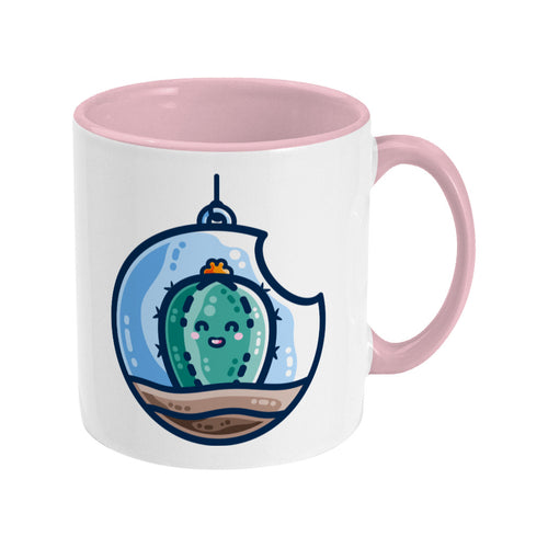 A two toned white and pale pink ceramic mug with the handle to the right showing a design of a kawaii cute happy green cactus succulent planted in a transparent hanging bauble terrarium.