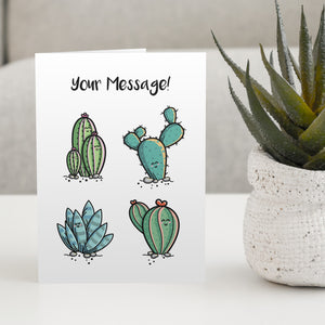 A white greeting card standing on a white table with a design of four kawaii cute cactus plants with the words your message written above