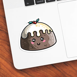 The corner of a laptop keyboard with a cute Christmas pudding die cut vinyl sticker stuck onto it