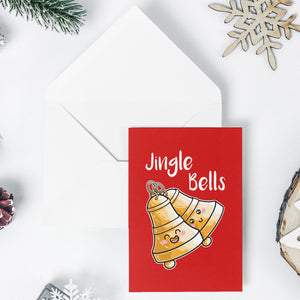 An open white envelope beneath a red greeting card with a design of two kawaii cute bells at an angle and the words 'Jingle Bells' written above