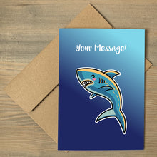 Load image into Gallery viewer, A blue greeting card lying flat on a brown envelope, with a design of a kawaii cute shark with personalised wording above