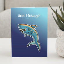 Load image into Gallery viewer, A blue greeting card standing on a white table, with a design of a kawaii cute shark with personalised wording above