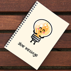 Closed notebook showing cream coloured front cover with light bulb design and personalisation