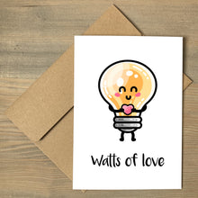 Load image into Gallery viewer, A white greeting card lying flat on a brown envelope, with a design of a kawaii cute lightbulb holding a heart and the words watts of love beneath