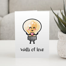 Load image into Gallery viewer, A white greeting card standing on a white table, with a design of a kawaii cute lightbulb holding a heart and the words watts of love beneath