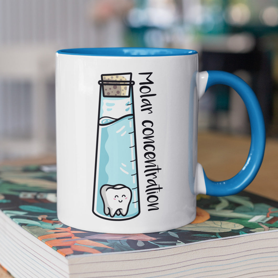 A corked chemistry vessel of liquid containing a molar tooth design on a two toned blue and white ceramic mug, showing RHS