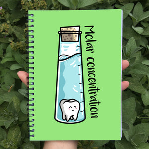Closed notebook showing green front cover with molar concentration wording and design