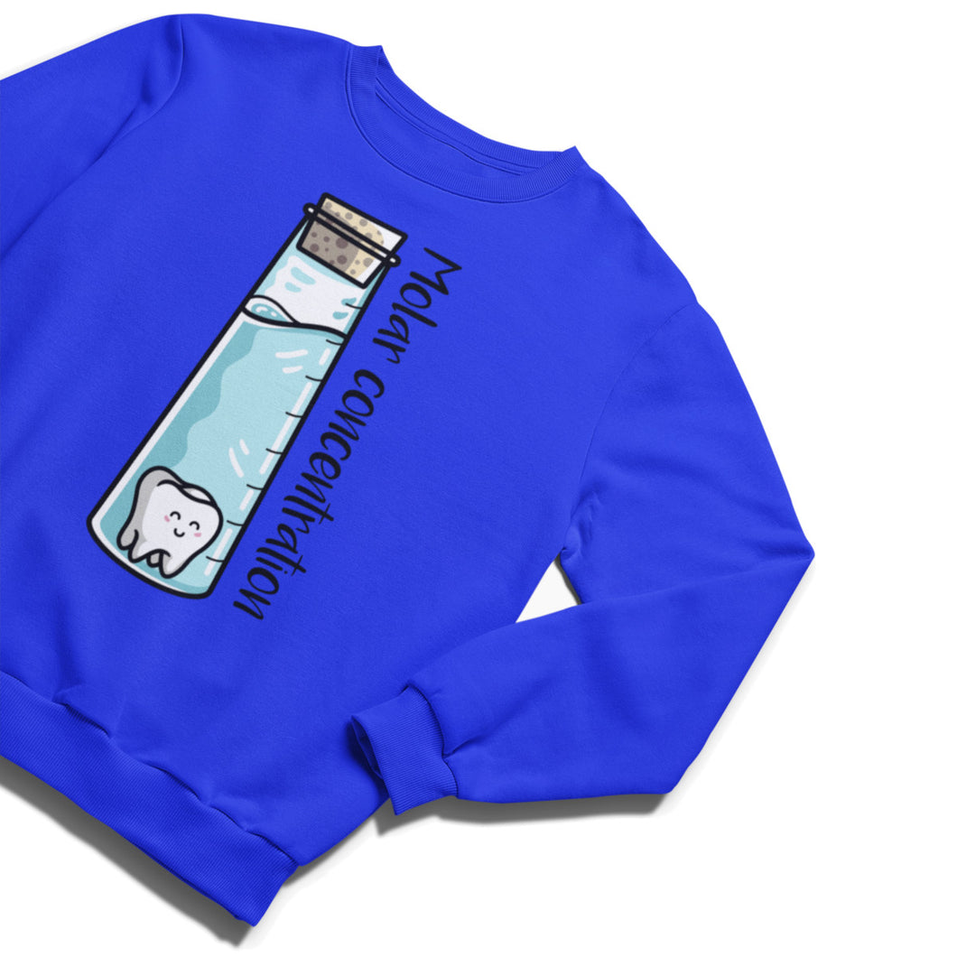 A royal blue unisex crewneck sweatshirt laid flat with a design on its chest of a tall tapering glass vessel with a cork stopper and blue liquid with a cute smiling molar tooth inside and he words molar concentration written down its side on the outside