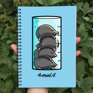 Closed notebook showing blue front cover with a design of 4 cute moles in a beaker