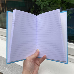 Hardback journal held open in a hand showing lined pages within