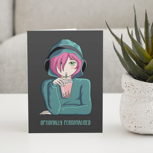 A dark grey greeting card standing on a white table with a design of a pink haired anime girl wearing a green hoodie and black headphones drinking pink boba bubble tea