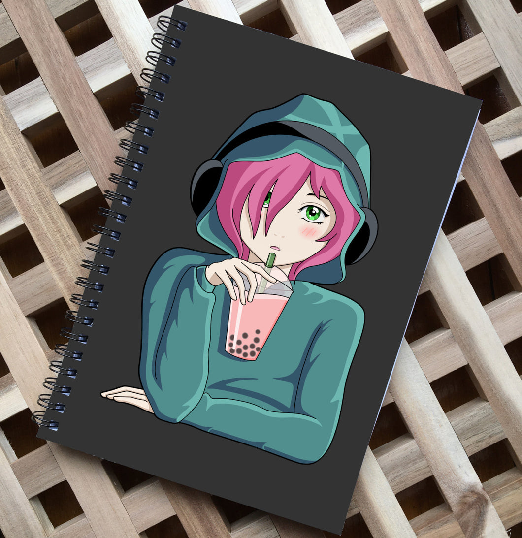 Spiral notebook lying flat on a wooden surface, has a dark grey front over featuring an anime girl wearing a green hoodie with the hood up and black headphones over the top, she has green eyes and pink hair and is holding a transparent plastic cup of pink boba with a green straw in her right hand which has her elbow resting on a surface, her left arm and hand is lying flat across her body in front of her on the surface as if she is sitting at a table