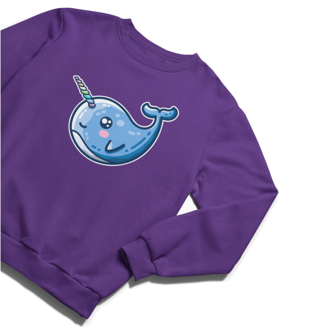 A purple unisex crewneck sweatshirt laid flat with a design on the chest of a kawaii cute narwhal with a rainbow striped horn