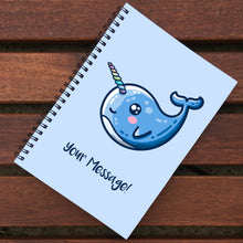 Load image into Gallery viewer, Closed notebook showing blue front cover with personalisation and cute narwhal design