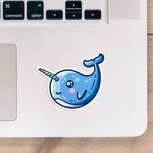 A shaped vinyl sticker of a smiling kawaii cute blue narwhal with a twisted rainbow striped horn, shown stuck onto the bottom right hand corner of a laptop computer keyboard