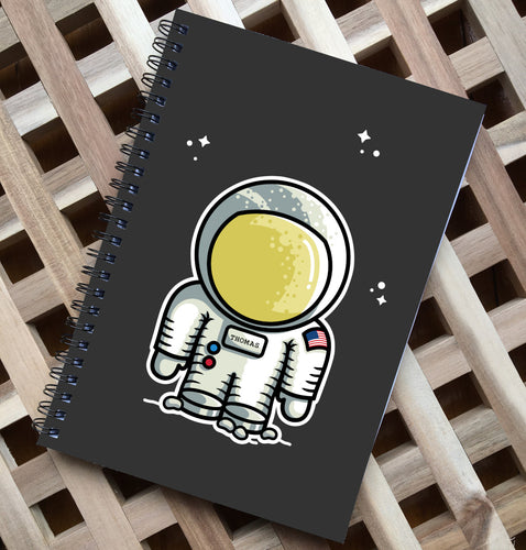 Black spiral notebook lying flat on a wooden surface, has a cute astronaut design printed on the center of the front cover with the name Thomas on its chest plate and some clusters of small white stars above and around the helmet