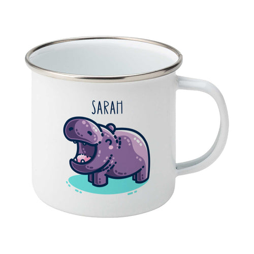 A white enamel mug with a silver rim, handle to the right. A name is written in thin dark blue upper case letters above a kawaii cute purple hippo with a thick dark blue outline and a turquoise shadow beneath. The hippo is seen side on facing to the left and looks happy with its mouth open wide.