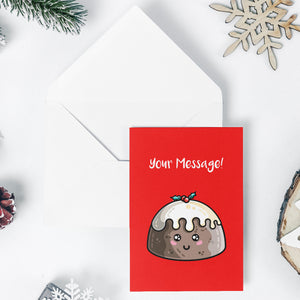An open white envelope beneath a red greeting card with a design of a kawaii cute smiling Christmas pudding with cream on top and a sprig of holly and your message in white above