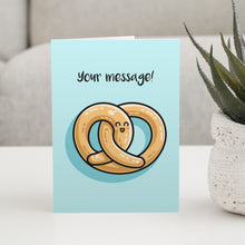 Load image into Gallery viewer, A pale turquoise greeting card standing on a table with a design of a kawaii cute pretzel and the words your message written above
