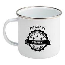 Load image into Gallery viewer, Personalised black circular banner design with the words 'terrific teaching assistant' on a silver rimmed white enamel mug, showing LHS