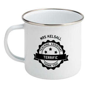 Personalised black circular banner design with the words 'terrific teaching assistant' on a silver rimmed white enamel mug, showing LHS