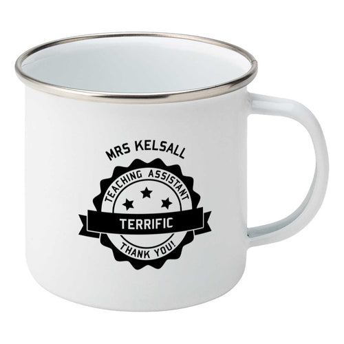 Personalised black circular banner design with the words 'terrific teaching assistant' on a silver rimmed white enamel mug, showing RHS