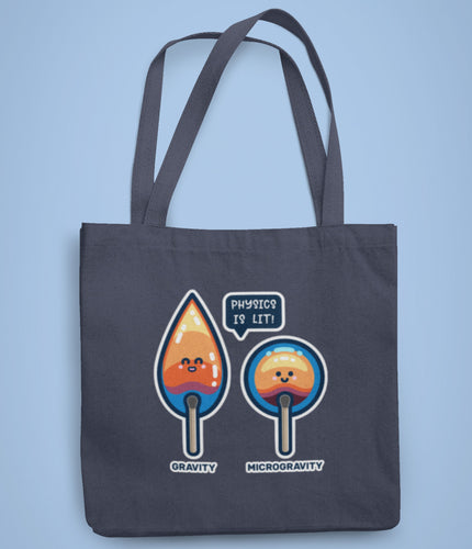 A dark blue coloured fabric tote bag lying flat against a pale blue background with a design in the center of two cute flames, one pointed with the word gravity and one circular with the word microgravity and a speech bubble saying physics is lit.