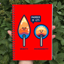 Load image into Gallery viewer, Held in a hand is a closed spiral notebook showing red front cover with a design of 2 cute flames, one pointed with word gravity and one round with word microgravity and speech bubble saying physics is lit!