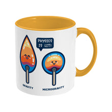 Load image into Gallery viewer, A yellow and white two toned ceramic mug with the handle to the right and a design of two cute flames, one pointed with the word gravity and one circular with the word microgravity and a speech bubble saying physics is lit
