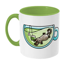 Load image into Gallery viewer, Cute platypus swimming in a glass teacup of green tea design on a two toned green and white ceramic mug, showing LHS