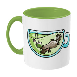 Cute platypus swimming in a glass teacup of green tea design on a two toned green and white ceramic mug, showing LHS